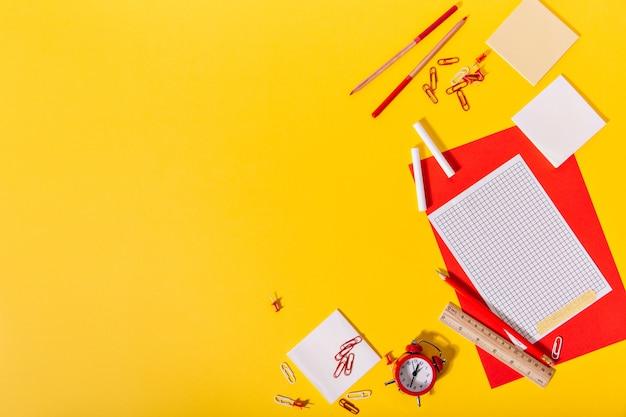 赤と紙、クリップ、クレヨン、鉛筆、木製の定規で構成される学校の文房具の明るいセット