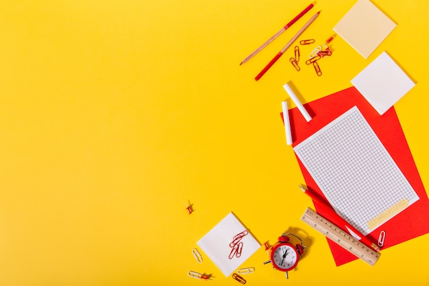 Bright set of school stationery consisting of red and paper, clips, crayons, pencils and wooden ruler