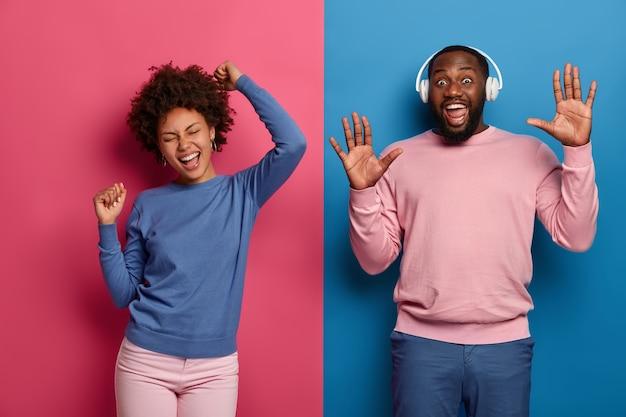 Colpo luminoso di energica coppia afroamericana felice danza con le braccia alzate, trascorrere il tempo libero in discoteca, utilizzare le cuffie