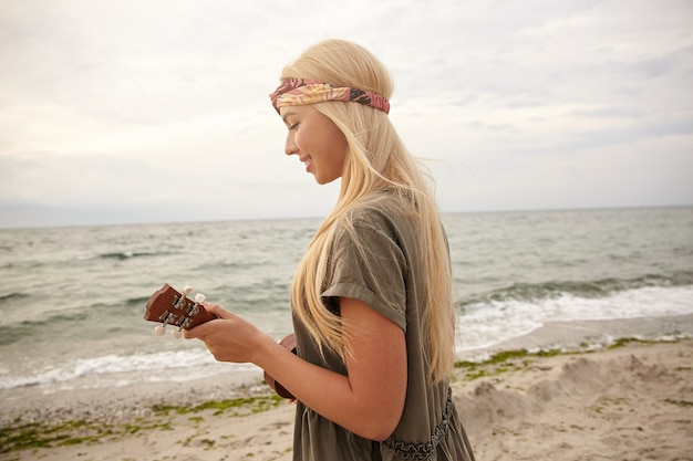 Bright shot of young attractive glad white-headed lady in headband dressed in romantic dress smiling while palying on ukulele against beach background