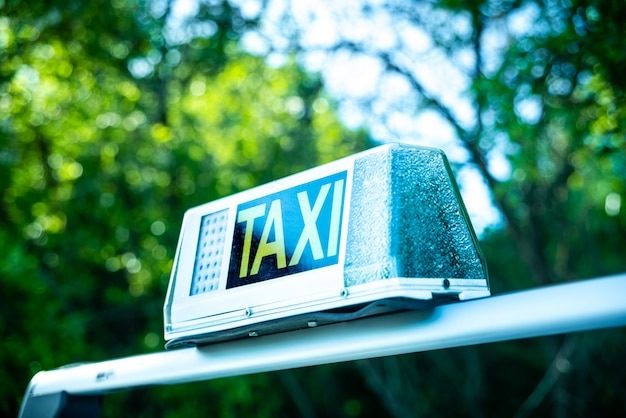 Bright sign with the word taxi on a car.