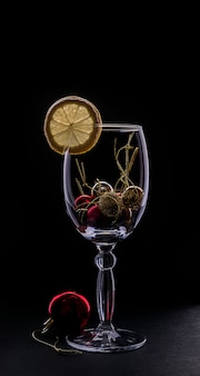 Bright silhouette of a glass with a slice of lemon and red christmas and new year ball on a dark background