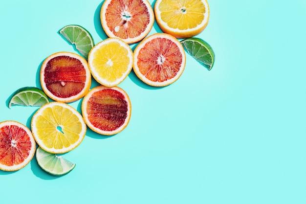 Яркие дольки цитрусовых, грейпфрута, красного апельсина, лимона, лайма на пастельном бирюзовом фоне