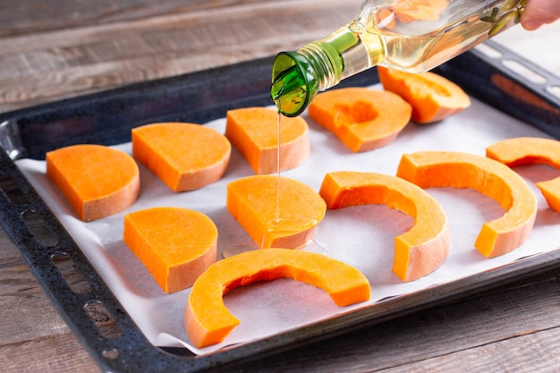 Bright slices of pumpkin prepared for baking in the oven with olive oil, food ingredient