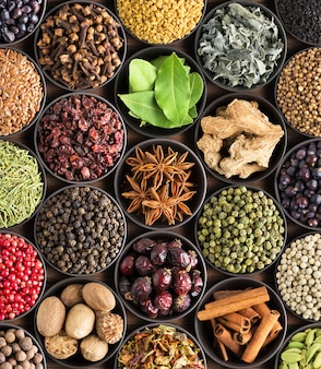 Bright  spices and herbs in cups, top view. background for packing with european condiments.