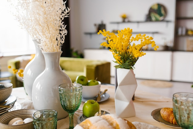 Bright spring mimosa in a ceramic geometric vase in the decor serving a festive or home table in the kitchen