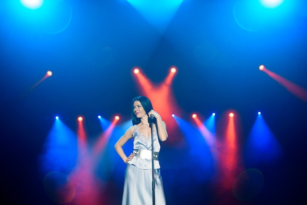 Bright stage lighting. vocalist singing to microphone.