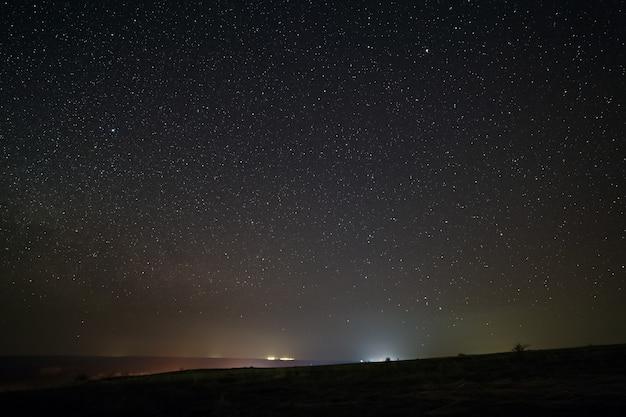 Яркие звезды в ночном небе с освещением от уличных фонарей города. световое загрязнение.