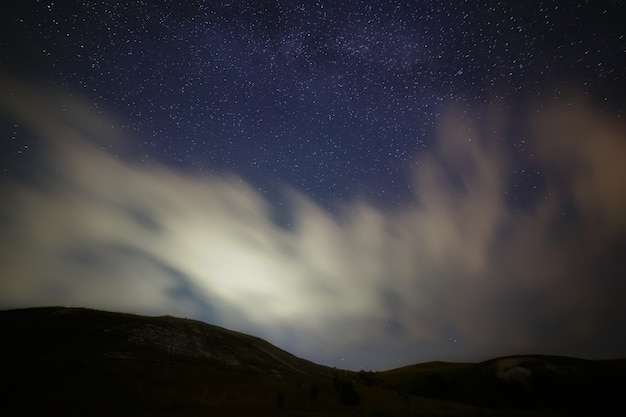 Bright stars in the night sky with clouds.