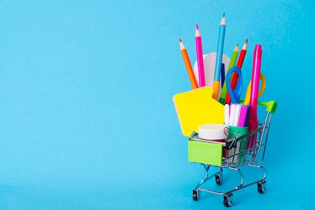 파란색 배경에 미니 슈퍼마켓 트롤리에 밝은 편지지 개체. 학교 개념으로 돌아 가기