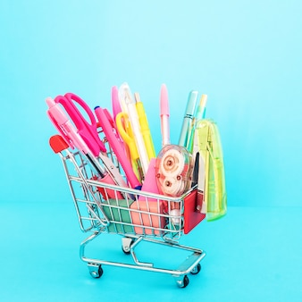 Bright stationery objects in mini shop cart on blue background. back to school concept.