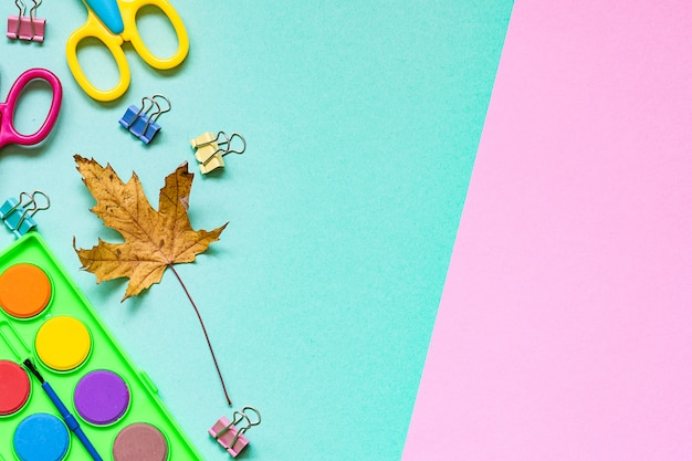 Bright stationery set and autumn maple leaf on two tone turquoise and pink background.