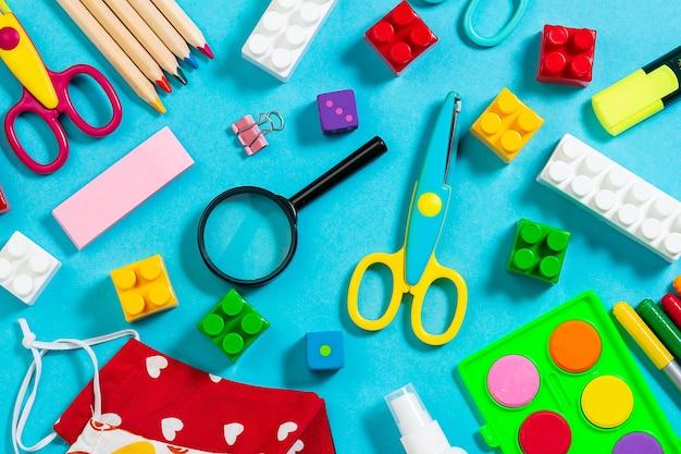 Яркие канцелярские товары и пластиковые конструкторы на вид сверху ярко-синем фоне.