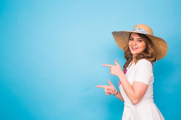 Яркий студийный портрет привлекательной молодой женщины, указывая copyspace на синем фоне.