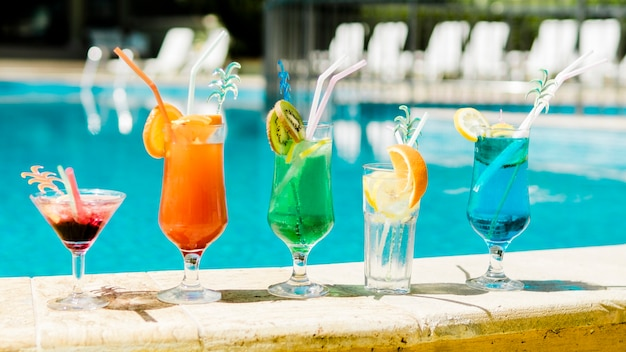 Bright summer cocktails near swimming pool