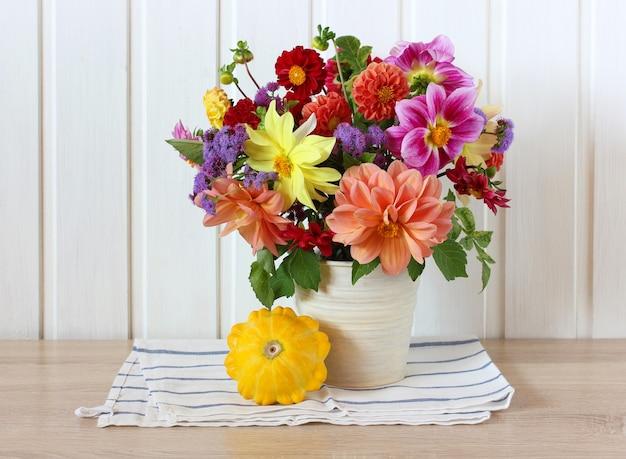 ガーデンダリアとスカッシュの明るい夏の構図。花と野菜。