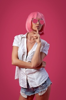Bright summer design concept. woman in a bright wig. close-up of a beautiful woman in a pink wig  in short attractive jeans, white shirt   posing on a pink background