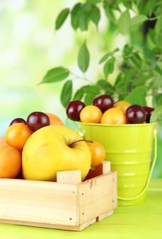 Яркие летние фрукты в ведре и деревянном ящике на деревянном столе на естественной поверхности