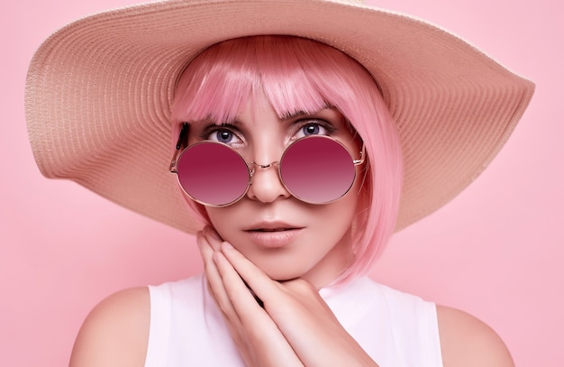 ピンクの髪、サングラス、カラフルなスタジオの編みこみの帽子を持つポジティブでゴージャスな女の子の明るい夏の肖像画