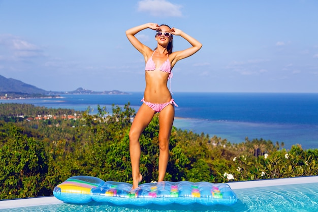 Bright summer portrait of young woman with perfect tanned slim body