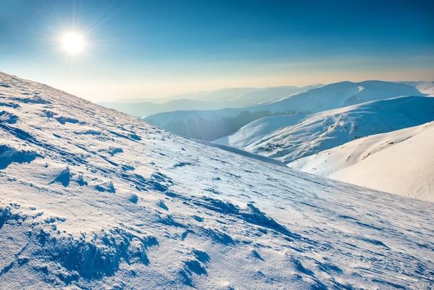눈으로 덮여 겨울 산에 밝은 태양