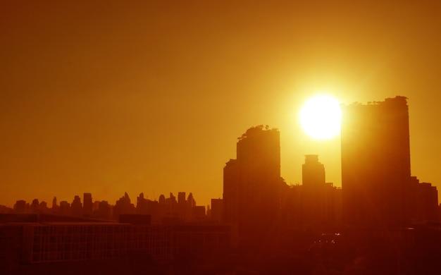 幻想的な黄金色の街のスカイラインの上の明るい太陽