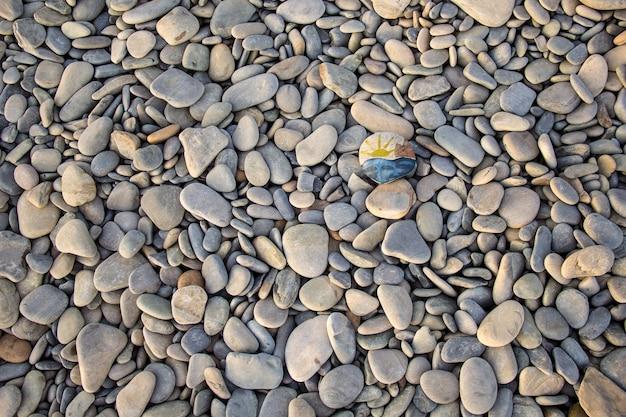 조약돌에 그려진 밝은 태양. 여름에 자갈과 바다 배경