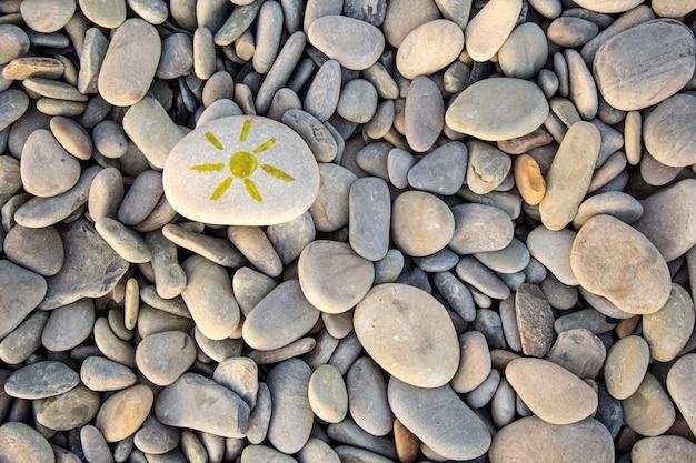 조약돌에 그려진 밝은 태양. 여름에 자갈 배경