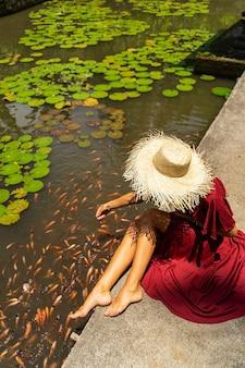 밝은 해. 모자로 머리를 보호하면서 물고기에게 먹이를 주는 동안 푸른 물을 바라보는 편안한 소녀