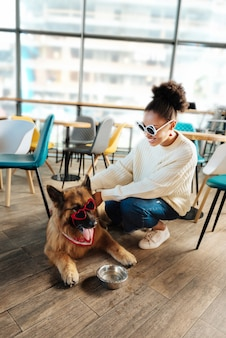 明るいサングラス。赤いハート型のサングラスで彼女の犬を養う明るいサングラスを身に着けている巻き毛のスタイリッシュな女性