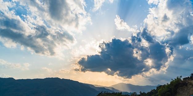 밝은 햇빛은 일몰 시간 동안 산맥의 어두운 장면에 구름 구멍을 통해 옵니다. 네팔 포카라의 일몰 풍경. 스톡 사진.
