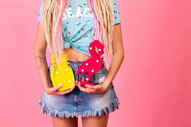 明るい日当たりの良いファッションの詳細、装飾的なパイナップルとフラミンゴを保持している若い女性