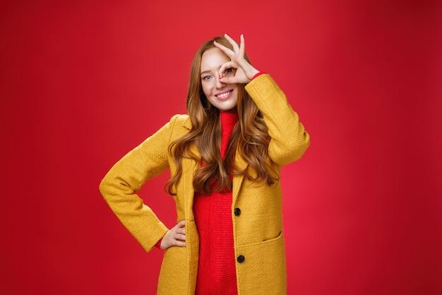 Ragazza brillante e solare che si sente felice anche nei giorni di pioggia in piedi con un cappotto elegante giallo su sfondo rosso che mostra un gesto ok sull'occhio, sorride ampiamente alla telecamera, tenendo la mano sulla vita.
