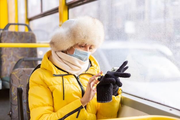 그녀의 손에 휴대 전화와 함께 겨울 날에 시내 버스에서 따뜻한 옷을 입고 젊은 여자의 밝고 맑은 초상화