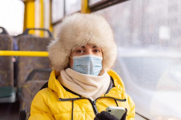 Ritratto luminoso e soleggiato di una giovane donna in vestiti caldi in un autobus urbano in una giornata invernale con un telefono cellulare in mano