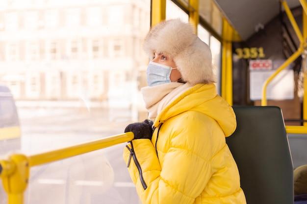 Ritratto luminoso e soleggiato di una giovane donna in vestiti caldi in un autobus urbano in una giornata invernale