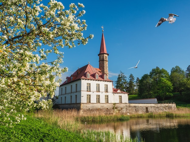 湖と古い白いマルタの城と明るい日当たりの良い春の景色。ガッチナ。ロシア。