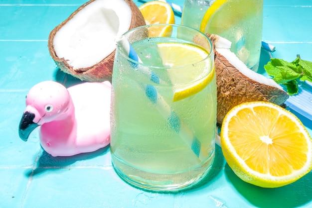 밝고 화창한 여름 휴가. 해변 휴가 액세서리, 플라밍고 구명 부표, 레몬, 코코넛, 민트, 열대 잎, 평평한 탑 뷰 복사 공간이 있는 젖은 파란색 수영장 타일 배경의 레모네이드 음료