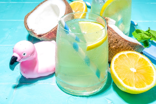 Bright sunny summer vacation. lemonade drink on wet blue pool tiles background, with beach holiday accessories, flamingo lifebuoys, lemons, coconuts, mint, tropical leaves, flatlay top view copy space