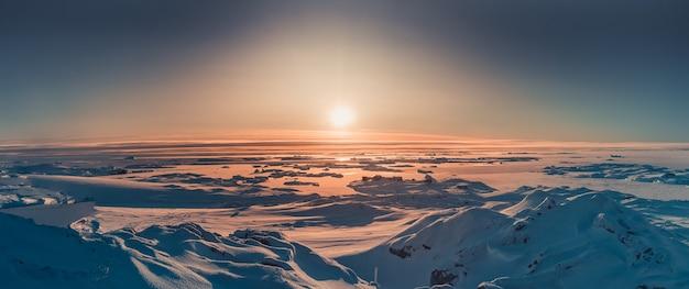雪に覆われた極地の表面上の南極オレンジ色の太陽の光の明るい夕日のパノラマビュー