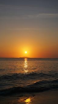 黄赤色のグラデーションカラーで海の下の明るい夕日-垂直