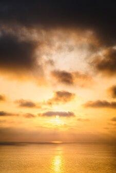 Яркий закат с большим желтым солнцем под поверхностью моря