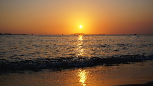 Яркий закат с желтым солнцем под поверхностью моря - летние каникулы и концепция приключений путешествия природы.
