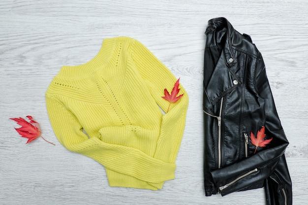 Яркий свитер, черный пиджак и листья