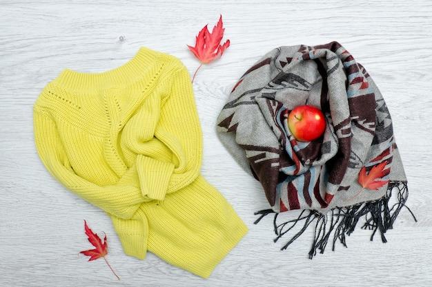Яркий свитер и шарф, красное яблоко, осенние листья