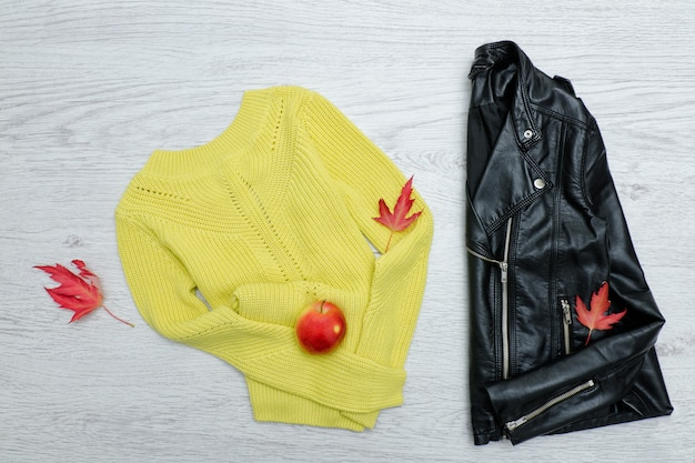 Bright sweater, a black jacket, a red apple and leaves