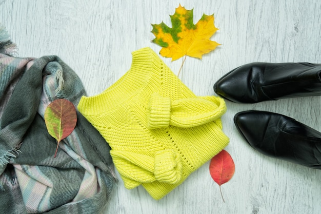 明るいセーター、スカーフ、黒いブーツ、そして紅葉。ファッショナブルなコンセプト