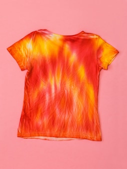 Bright t-shirt in tie dye style. flat lay. staining fabric in tie dye style. flat lay.