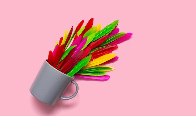 Яркая чайная композиция. серая кружка с цветными перьями.