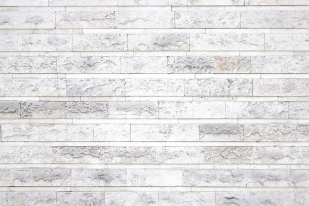 石のブロックの明るい質感、背景として白いインテリア